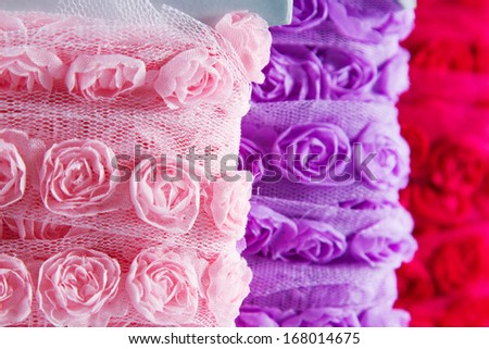 Pretty ribbons with rose patterns in a light mesh material. Focus on the pink reel in the foreground. - stock photo