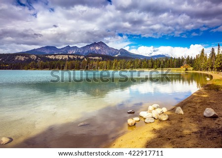 Pretty round lake in the coniferous forest. Canadian Rocky Mountains, Jasper National Park, lake Annette - stock photo