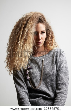 pretty sad girl with a blond afro hair - stock photo