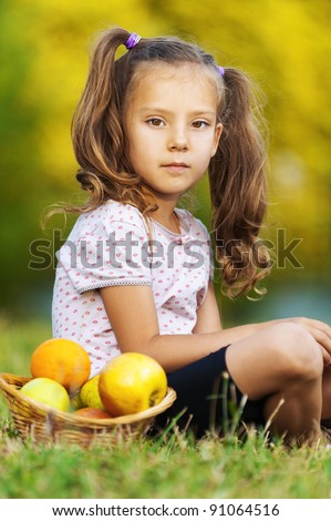 pretty sad portrait of child ( girl), sitting on green grass (meadow) with wicker basket with fruits (apples, oranges) - stock photo