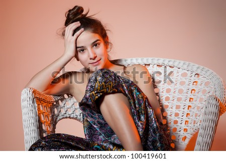 Pretty sad teen girl sitting in a chair looking at the camera - stock photo