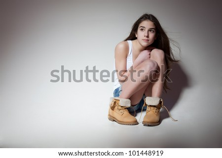 pretty sad teenage girl sitting on a white background - stock photo