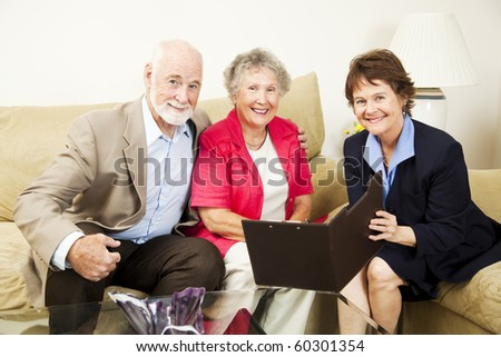 Pretty saleswoman meets with happy senior couple in their home. - stock photo