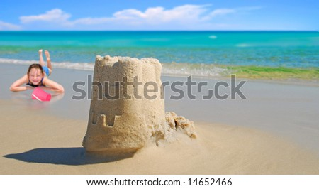 Pretty sand castle built by young girl at seashore - stock photo