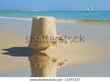 Pretty sand castle by tidepool with sailboat on ocean in distance - stock photo