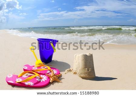 Pretty sand castle on seashore by beach accessories - stock photo