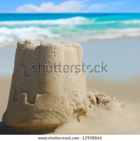Pretty sand castle with ocean in distance - stock photo