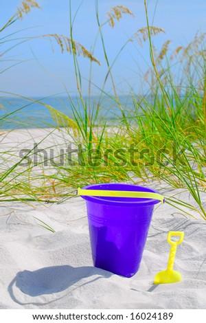 Pretty sand dune with beach bucket - stock photo