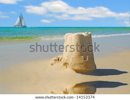 Pretty sandcastle by tidepool with sailboat under pretty sky - stock photo