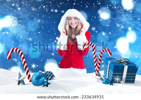 Pretty santa girl smiling at camera against christmas scene with gifts and candy canes - stock photo