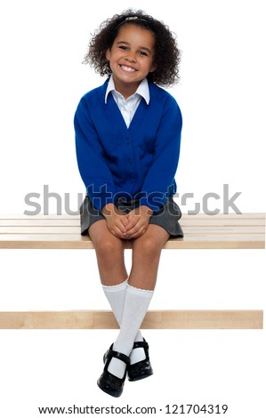 Pretty school girl seated comfortably on a bench with her legs crossed. - stock photo