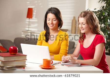 Pretty schoolgirls learning at home looking at laptop computer at table smiling.? - stock photo