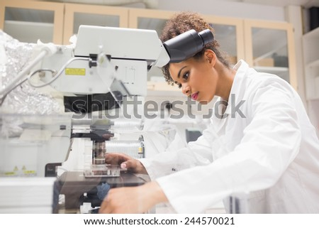 Pretty science student using microscope at the university - stock photo