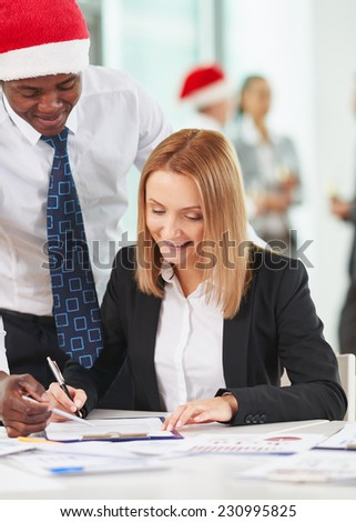 Pretty secretary going to sign document with African-american co-worker near by on background of their business partners - stock photo