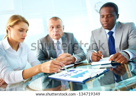 Pretty secretary pointing at paper while explaining something to her boss and colleague - stock photo
