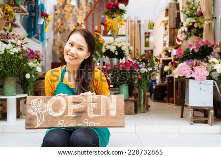 Pretty seller of the shop sitting with Open sign - stock photo