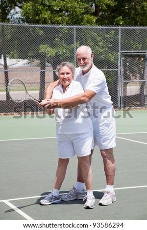 Pretty senior woman gets tennis instruction from a handsome senior man. - stock photo