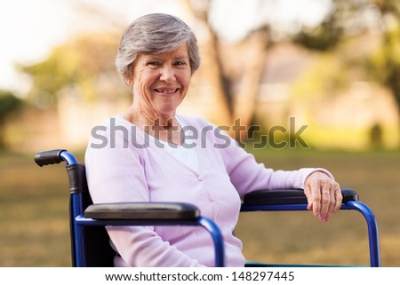 pretty senior woman sitting on wheelchair outdoors  - stock photo