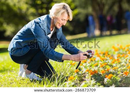 pretty senior woman taking photographs of flower in a spring garden - stock photo