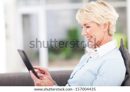 pretty senior woman using tablet computer at home - stock photo