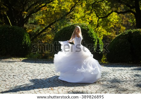 Pretty sensual thoughtful young bride girl with long blonde hair in beautiful white wedding dress standing outdoor on spring natural background, vertical picture - stock photo