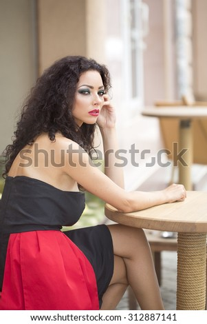 Pretty sensual young woman with fashion makeup curly brown hair wearing black and red dress with bare shoulders looking away sitting at wooden table in profile outdoor on blur background, vertical  - stock photo