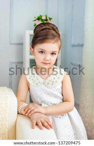 Pretty serios little lady in interior - stock photo