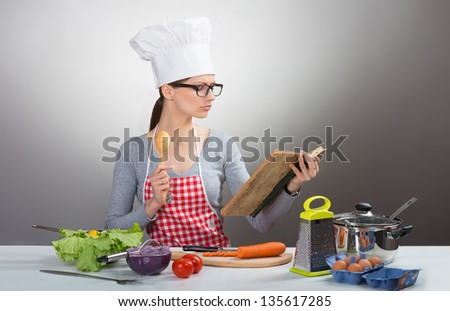 Pretty serious woman cooking with old cookbook on grey background - stock photo