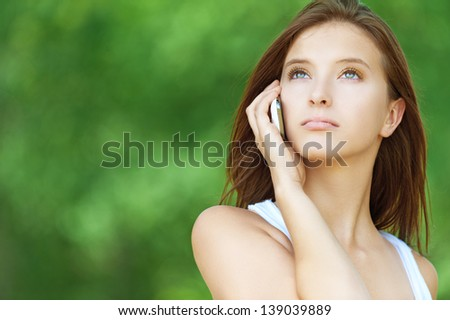 pretty serious young woman short hair talking phone summer park - stock photo