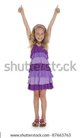 Pretty seven year old girl with arms extended overhead giving thumbs up gesture on white background. - stock photo