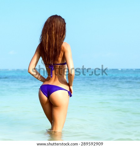 Pretty sexy brunette woman in blue bikini posing in the water on the sea beach and have fun on blue background  - stock photo