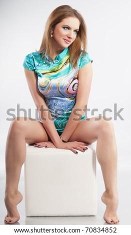 Pretty sexy fashion girl sitting on a white cube - stock photo