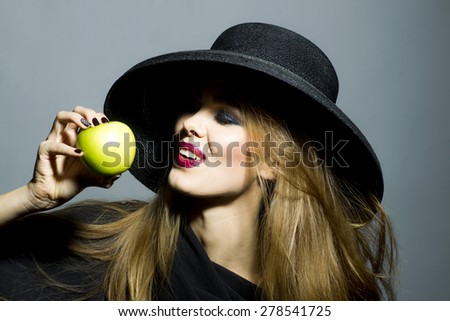 Pretty sexy girl in retro black hat with bright make up biting fresh green apple standing on gray background copyspace, horizontal picture - stock photo