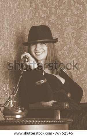 Pretty sexy woman in a hat is sitting and talking on an old telephone. Retro style