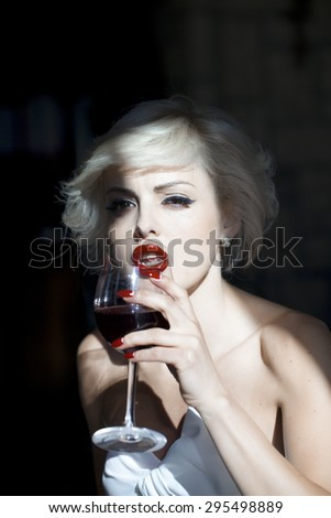 Pretty sexy young blond woman with bright makeup drinking red wine from glass looking forward, vertical picture - stock photo