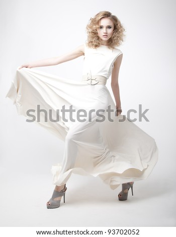 Pretty sexy young woman blonde with flying ivory dress isolated over white background - stock photo
