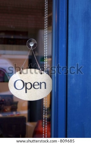 "Pretty shop sign saying ""open"" against a blue door - retail and shopping image - stock photo"