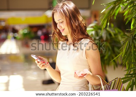 Pretty shopper reading sms about new sale or offer - stock photo
