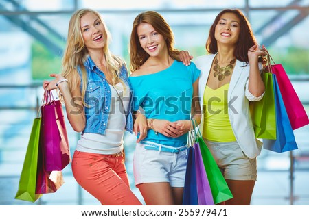 Pretty shoppers with paperbags in stylish casualwear - stock photo