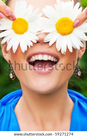 pretty shy girl hide her eyes with camomiles outdoors - stock photo