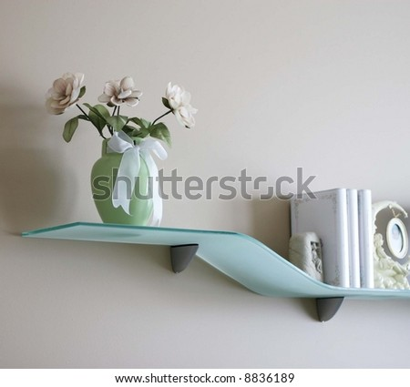 Pretty silk flowers in a vase on a glass shelf - stock photo