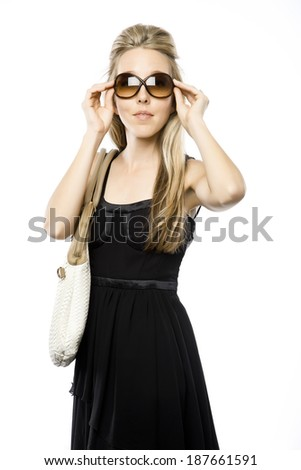 Pretty slender blond with purse on your shoulder and large sunglasses, looking straight ahead - stock photo