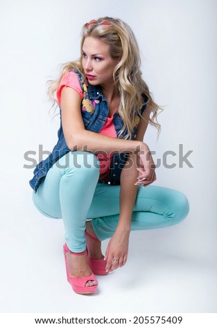Pretty slim blond woman model wearing bright pink top, denim vest, turquoise pants and stylish platform shoes, posing, sitting, looking aside. Over white background - stock photo
