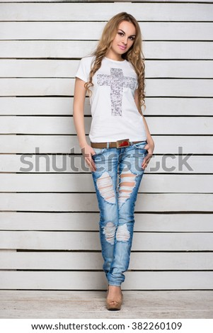 Pretty slim blonde in jeans and t-shirt posing near the white wooden wall - stock photo
