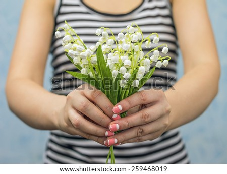 Pretty slim girl holding lilies of valley, close-up - stock photo