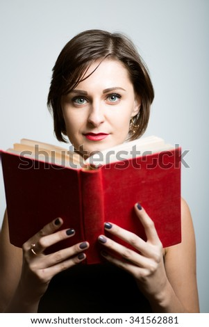Pretty slim girl reads the red book, bright photo lifestyle, photo studio on isolated gray background