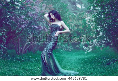 pretty slim girl with dark hair in a long emerald green dress with bare shoulders is in the garden with blooming lilac bushes