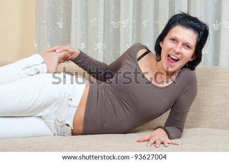 Pretty slim woman lying on the couch and laughing.