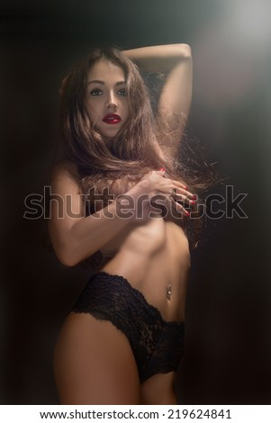 pretty slim woman shows her perfect body in light rays - stock photo