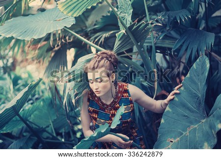 Pretty slim young girl in unusual multicolored summer dress with green eyebrows in the tropical jungles of Southeast Asia Votochnoy among large leaves and vines
